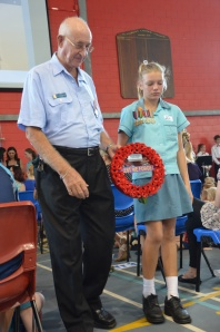 Photo taken at St Andrews College 24th April 2013 Neil Howard EXRAAF now the current RAAFA Cairns Branch Treasurer with his Granddaughter Cassidy Bromley placing a wreath on behalf of RAAFA at St Andrews College Cairns at the Anzac Day Service held at the school. Cassidy is wearing her Great Grandfather's, and Neil's father (Jack Howard ex RAAF WWII) service medals.